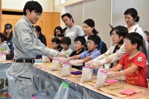セメントと砂の入った袋に、学生が水を入れていきます。
