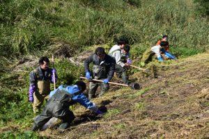 斜面のゴミを回収する学生たち